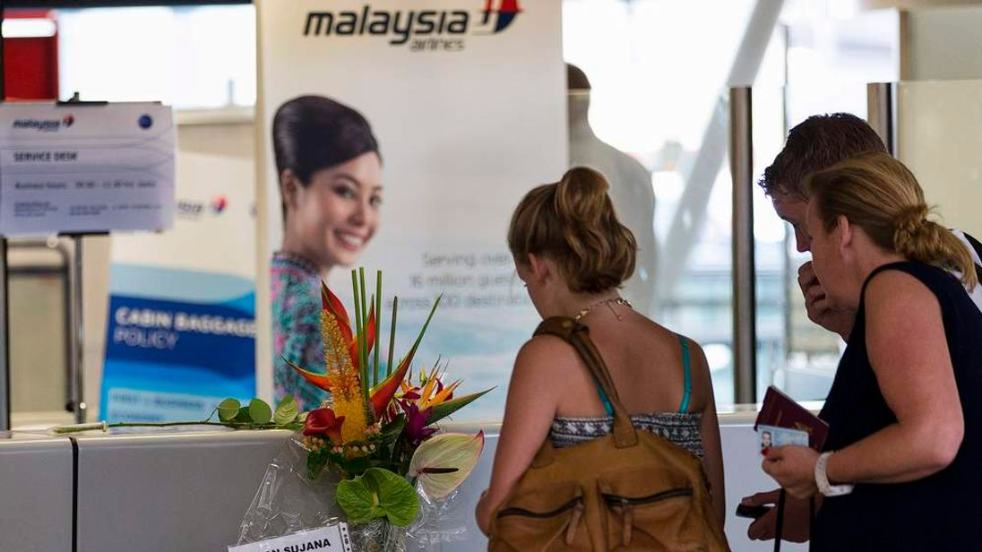 Women look at note placed with a bouquet of flowers on a Malaysia Airlines counter at Schiphol Airport