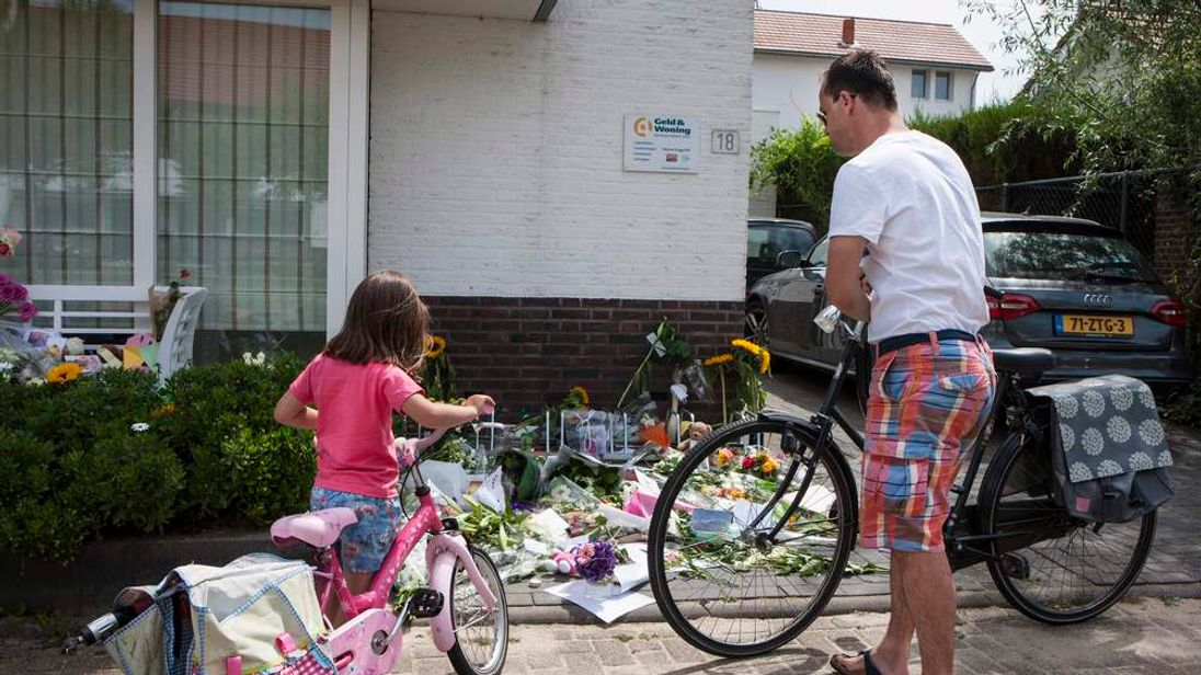 A father and his daughter look at flowers in front of the house of a family, who were all killed in Malaysia Airlines flight MH17 crash, in Rosmalen