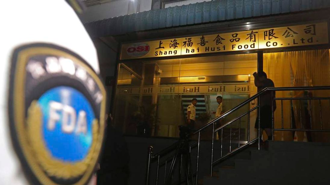 Officers from Shanghai Food and Drug Administration conduct a seizure at Husi Food factory in Shanghai