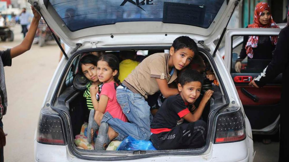 Palestinian children sit in a car boot as they flee their family homes following heavy Israeli shelling during an Israeli ground offensive east of Khan Younis, in the southern Gaza Strip