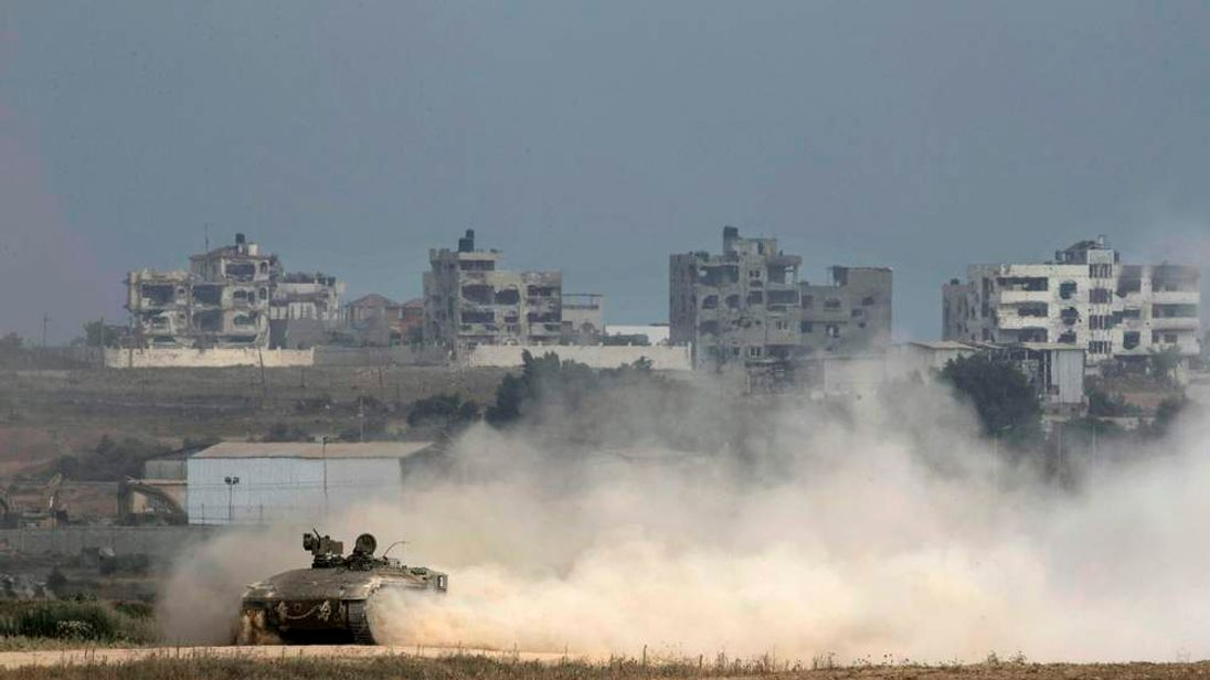 An Israeli armoured personnel carrier drives back into Israel after crossing the border with the northern Gaza Strip