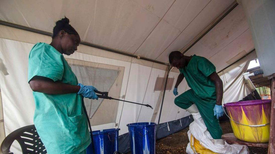 A health worker removes his protective suit as he emerges from an isolation area at the Medecins sans Frontieres Ebola treatment centre in Kailahun