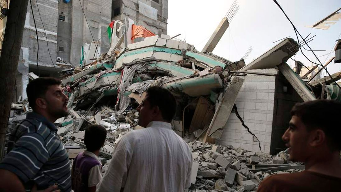 Palestinians stand by the rubble of the home of Hamas Gaza leader Ismail Haniyeh in Gaza City