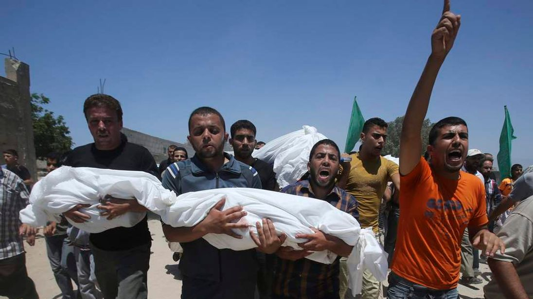 Mourners carry the bodies of Palestinian children during their funeral in Khan Younis in the southern Gaza Strip