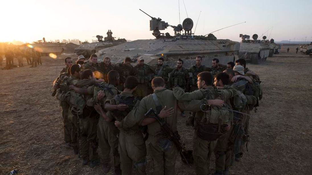 Israeli soldiers from the Golani Brigade stand in a circle at a staging area before entering Gaza from Israel