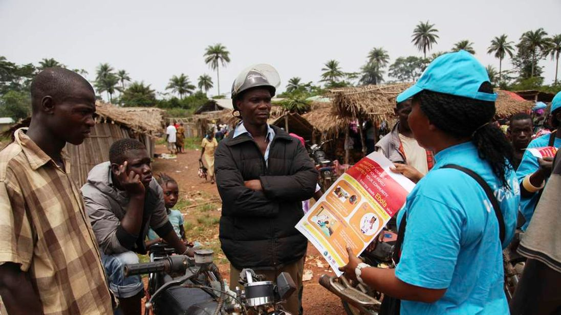 A UNICEF worker speaks with drivers of motorcycle taxis  about the symptoms of Ebola virus disease (EVD) and best practices to help prevent its spread, in the city of Voinjama, in Lofa County in this handout photo