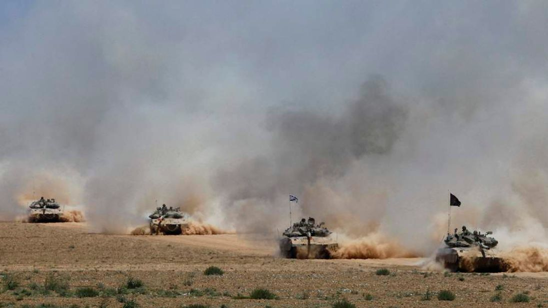 Israeli soldiers ride tanks after returning to Israel from Gaza