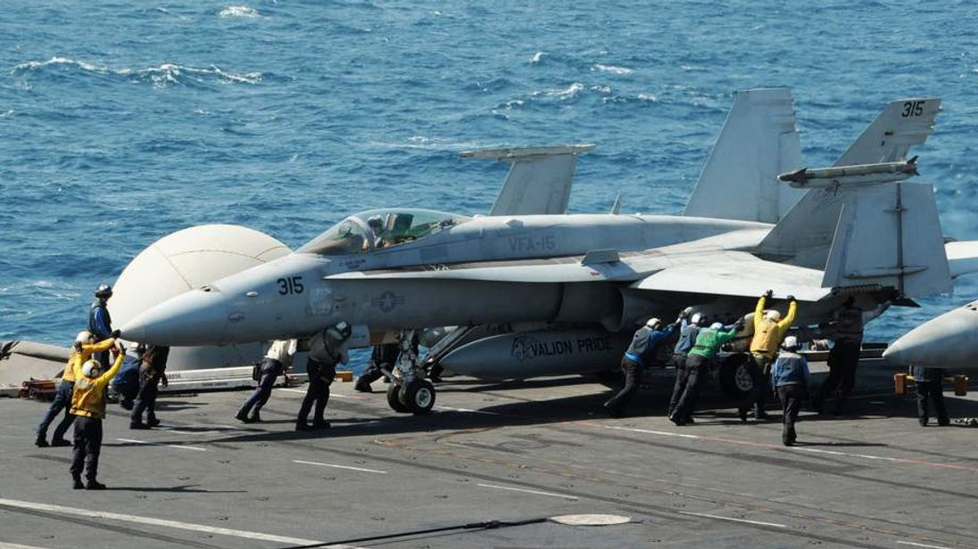 Handout photo shows sailors guiding an F/A-18C Hornet on the flight deck of the aircraft carrier USS George H.W. Bush in the Gulf