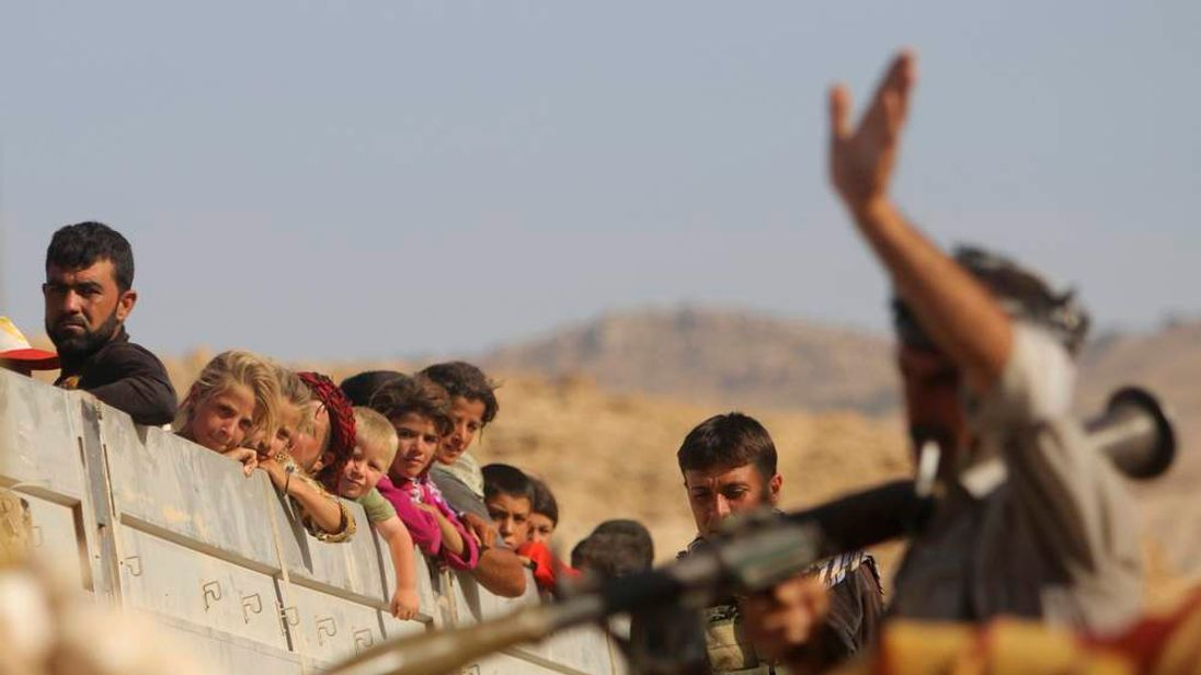 A Yazidi fighter who recently joined the Kurdish People's Protection Units gestures while securing a road in Mount Sinjar