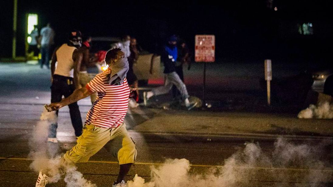 A protester picks up a gas canister to throw back towards the police after tear gas was fired at demonstrators who are continuing to react to the shooting of Michael Brown in Ferguson, Missouri