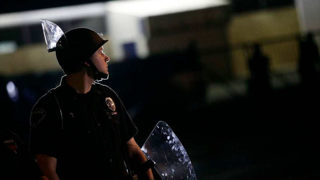 A police officer in riot gear stands in position as demonstrators protest the shooting death of Michael Brown in Ferguson