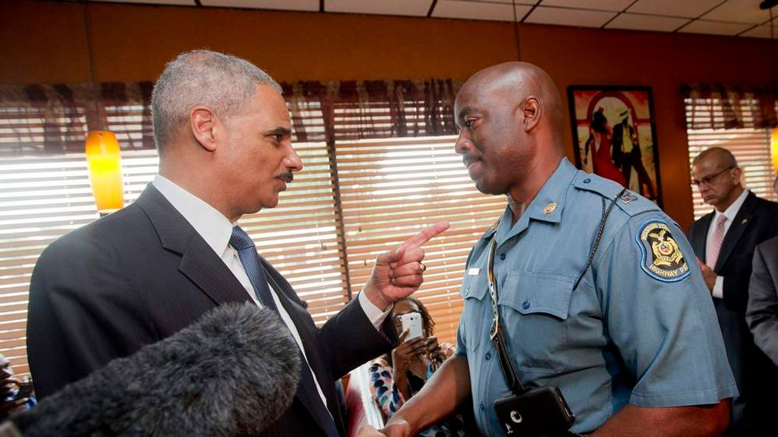 Attorney General Eric Holder talks with Capt. Ron Johnson of the Missouri State Highway Patrol at Drake's Place Restaurant in Florrissant