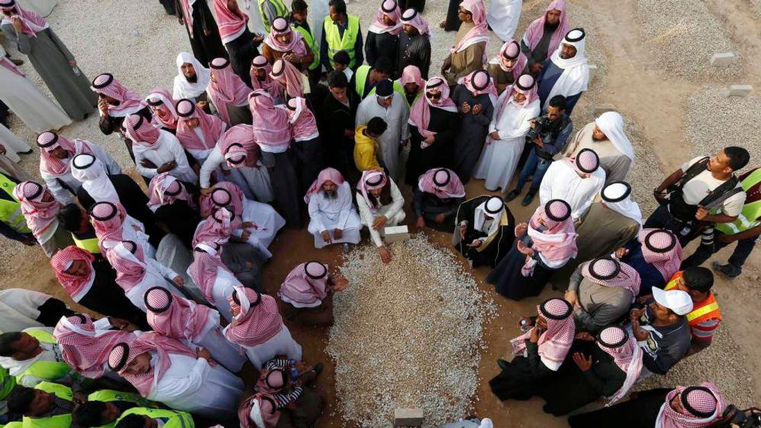 Mourners gather around the grave of Saudi King Abdullah following his burial in Riyadh
