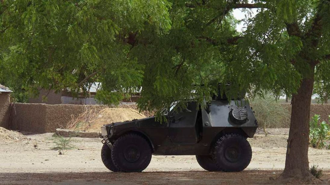 A military armoured vehicle is stationed under a tree during a military patrol in Hausari village