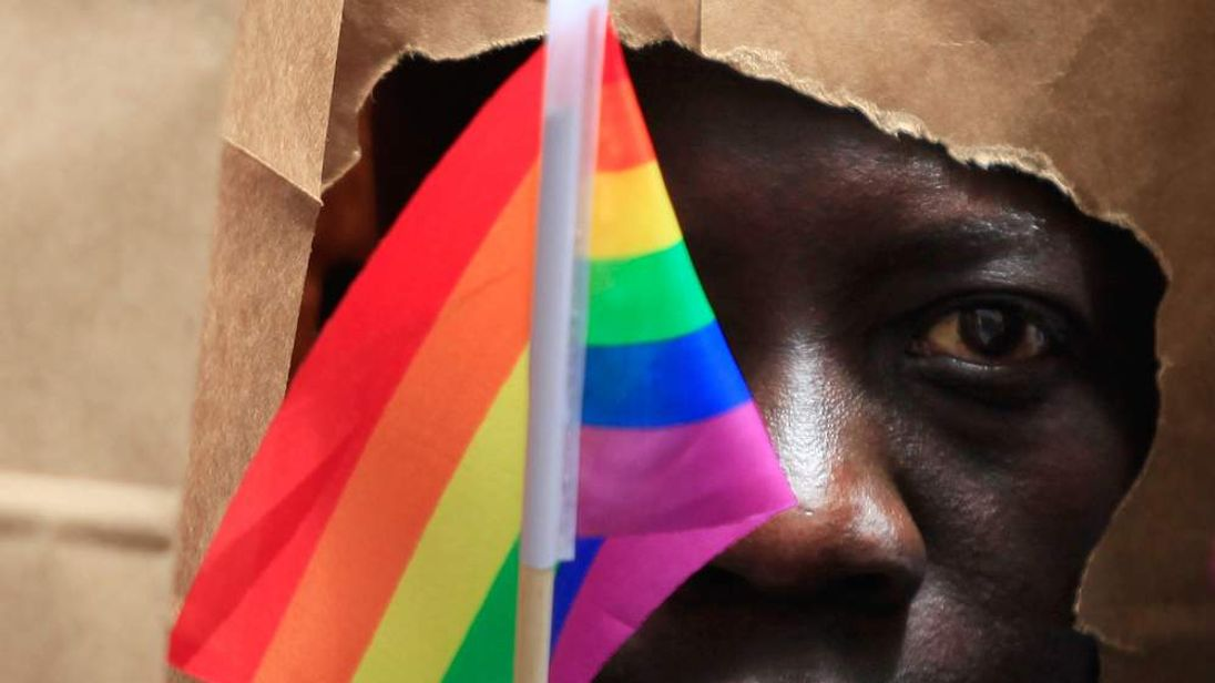 An asylum seeker from Uganda covers his face with a paper bag in order to protect his identity as he marches with the LGBT Asylum Support Task Force during the Gay Pride Parade in Boston