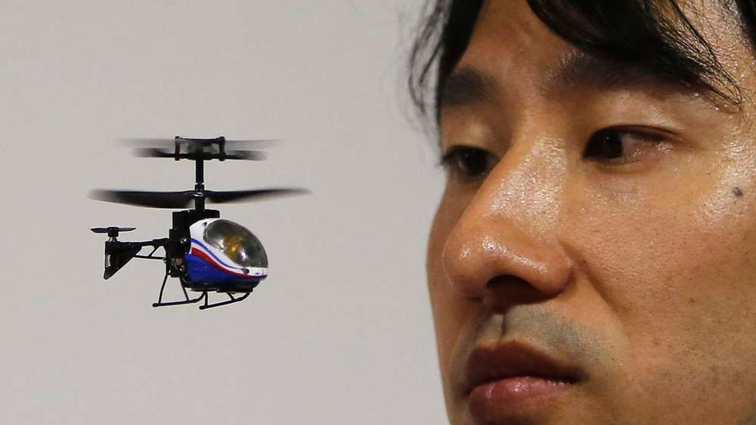 "An employee of Japanese toymaker CCP Co. looks at the company's ""NANO-FALCON"" at the International Toy Show in Tokyo"