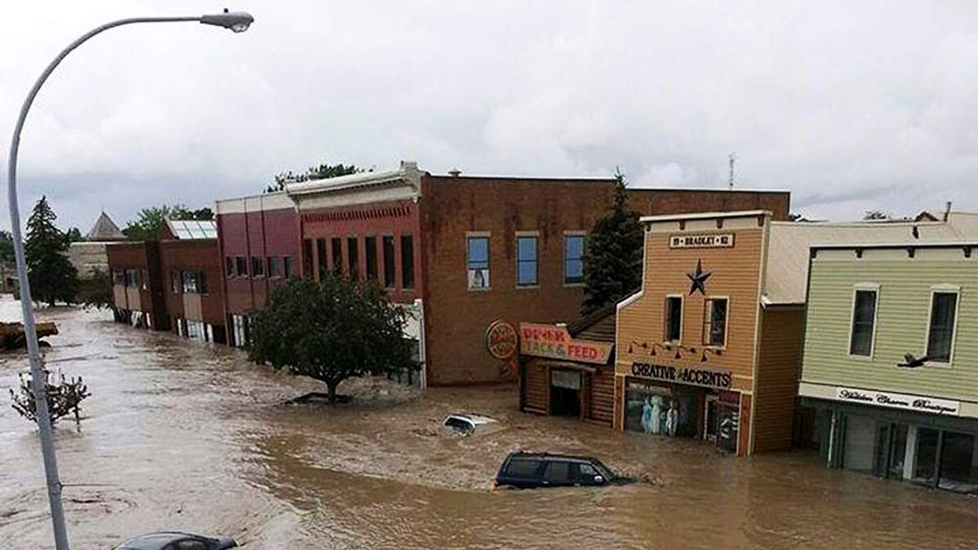 Cars in the water covering a downtown street in High River, Alberta.