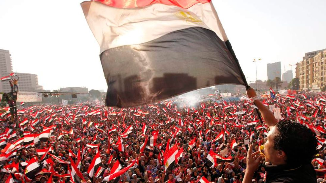 Protesters against Egyptian President Mohamed Mursi wave national flags in Tahrir Square in Cairo
