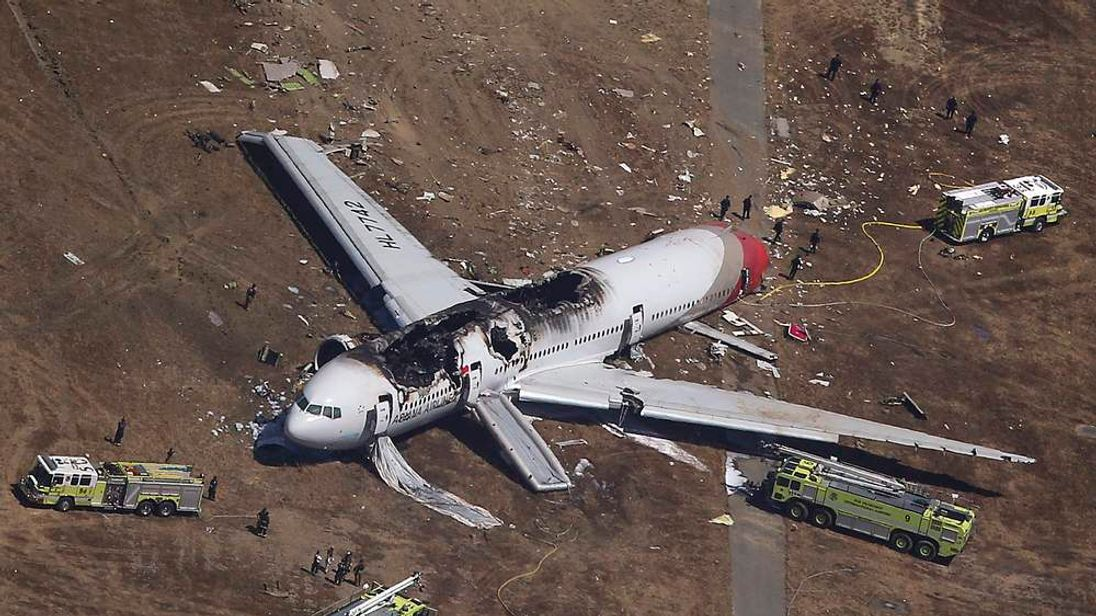 Search and rescue officials surround an Asiana Airlines Boeing 777 plane after it crashed while landing at San Francisco International Airport in California