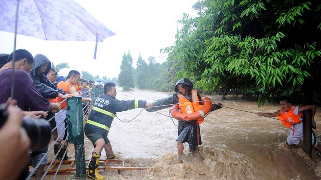 Firefighters use a rope to help a woman walk across floodwaters after heavy rainfalls hit Dujiangyan