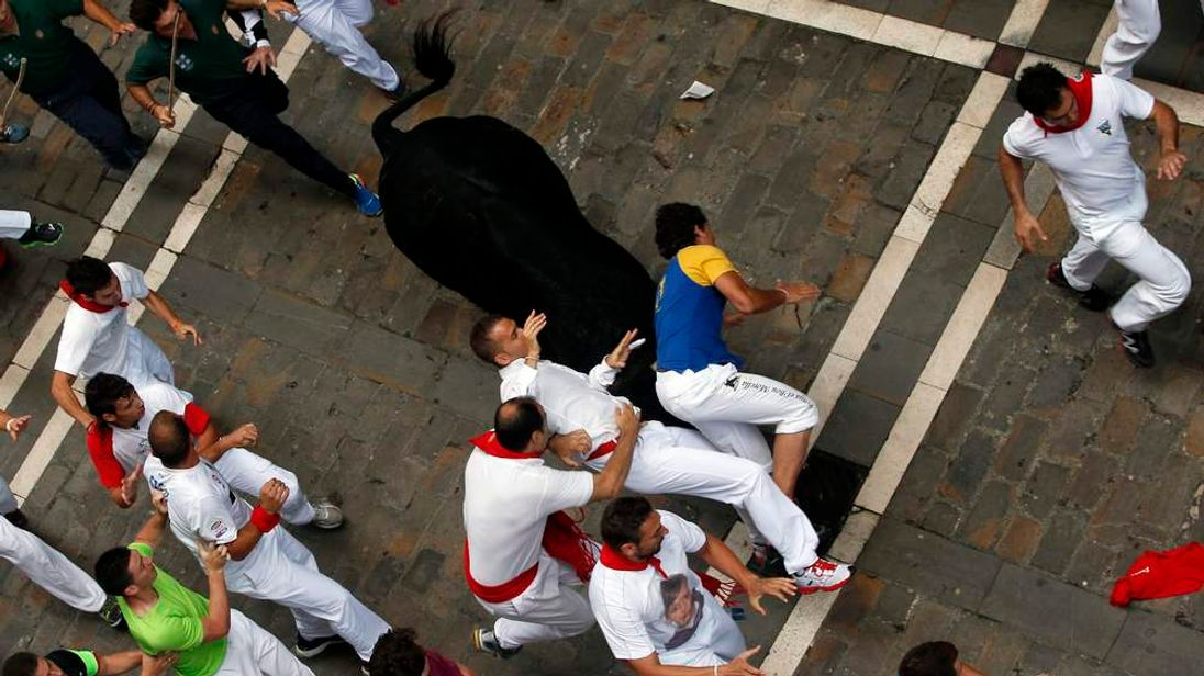 An El Pilar fighting bull charges at runners during the sixth running of the bulls of the San Fermin festival in Pamplona