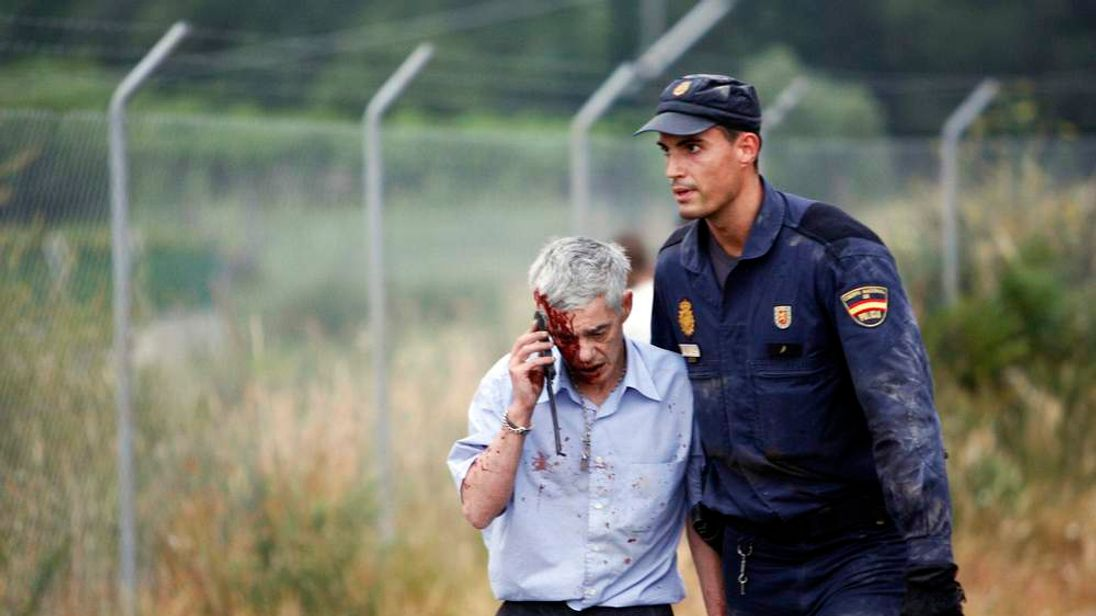 An injured passenger is helped by a policeman after a train crashed near Santiago de Compostela