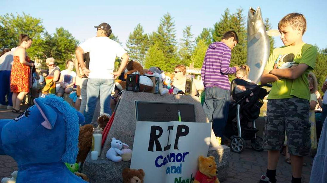 Allen Long looks at a makeshift memorial during a vigil for Noah and Connor Barthe in Campbellton New Brunswick