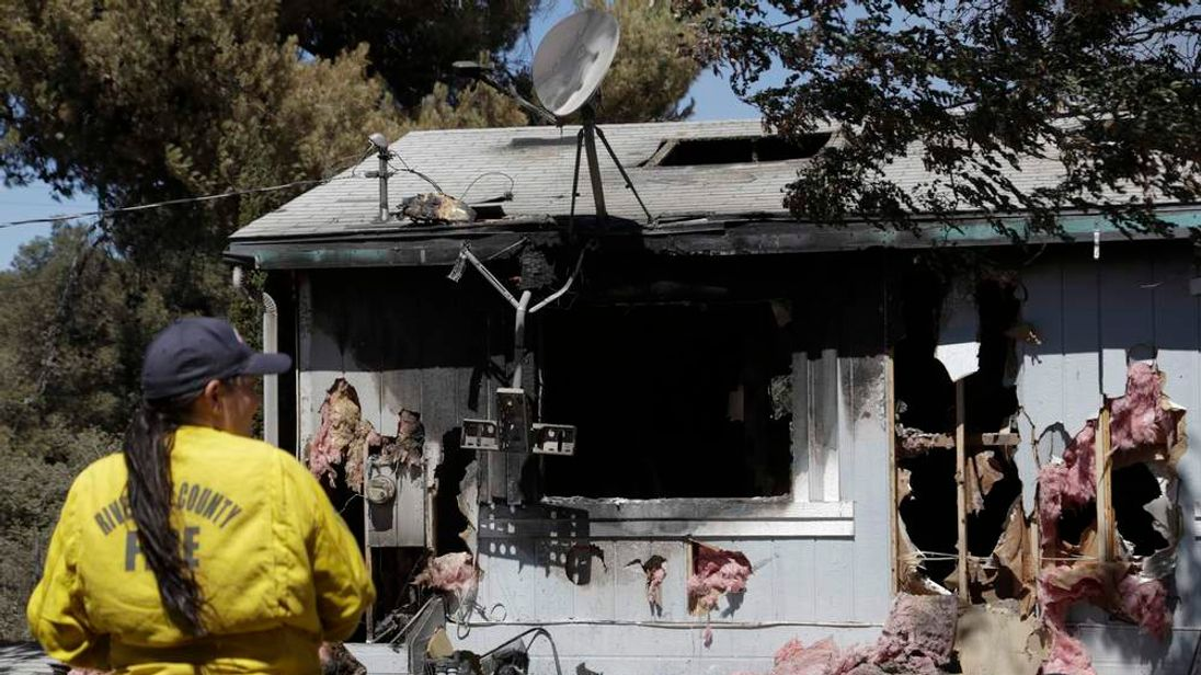 Zuzzette Bricker of the Office of Emergency Services surveys a fire-damaged home after the Silver Fire spread along California Route 243 the night before near Banning, California