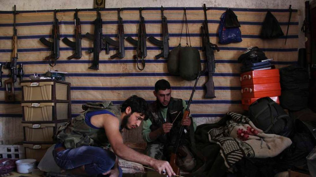 Free Syrian Army fighters sit inside a weapons warehouse in Kansafra
