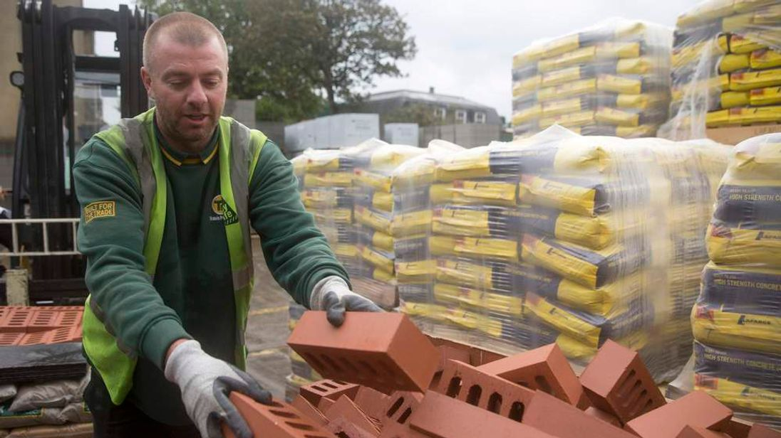A worker stacks bricks at the Vauxhall depot of building material supplier Travis Perkins in London