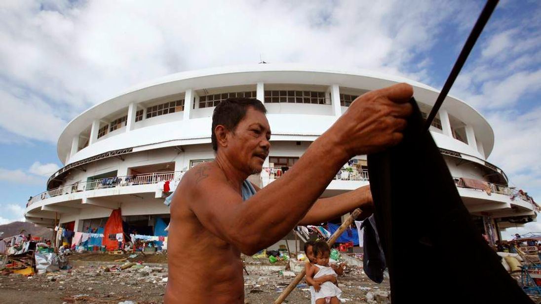 A man hangs his clothes out to dry in the aftermath of super typhoon Haiyan, in Tacloban