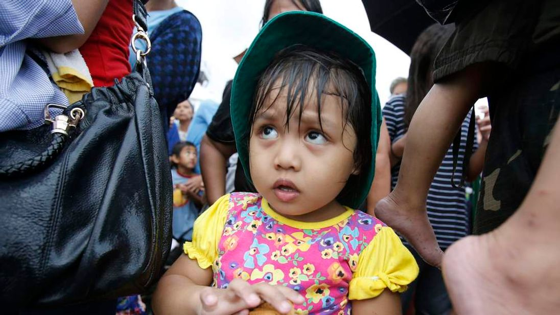 A girl waits to be airlifted to Manila in the aftermath of super typhoon Haiyan at Tacloban airport