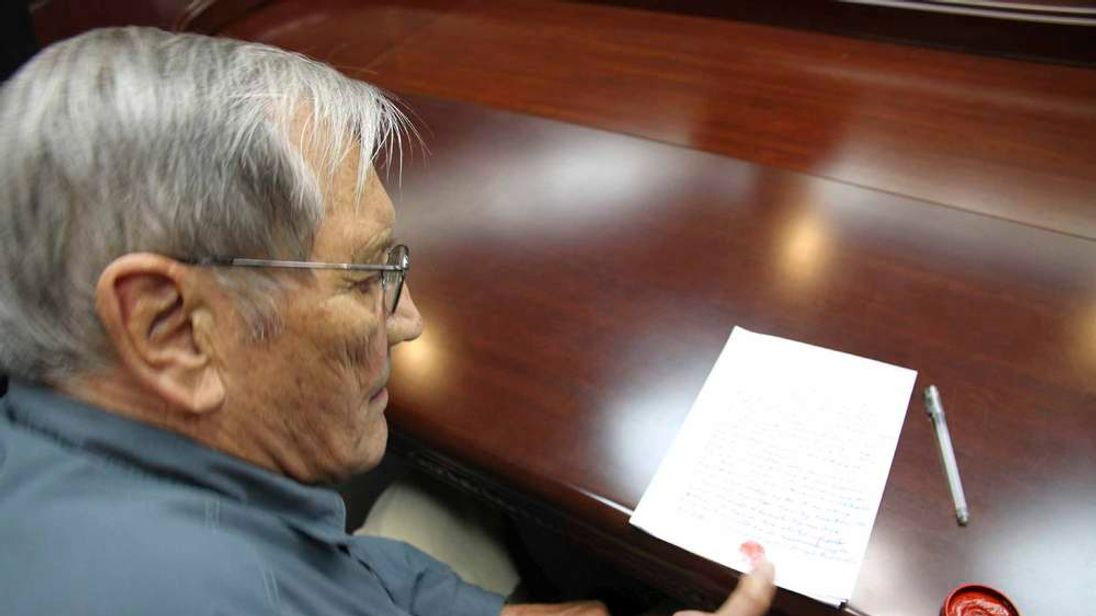 KCNA handout shows U.S. citizen Newman putting his thumbprint on a piece of paper at an undisclosed location in North Korea