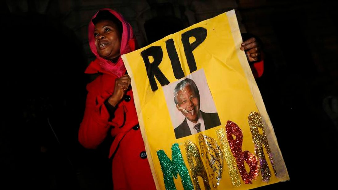 Woman holds a sign at a gathering in memory of Nelson Mandela outside the South African High Commission across from Trafalgar Square in London