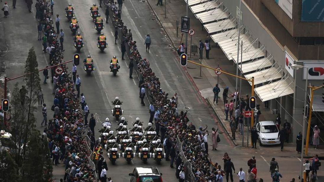 Military outriders escort funeral cortege carrying coffin of former South African President Mandela through street of Pretoria