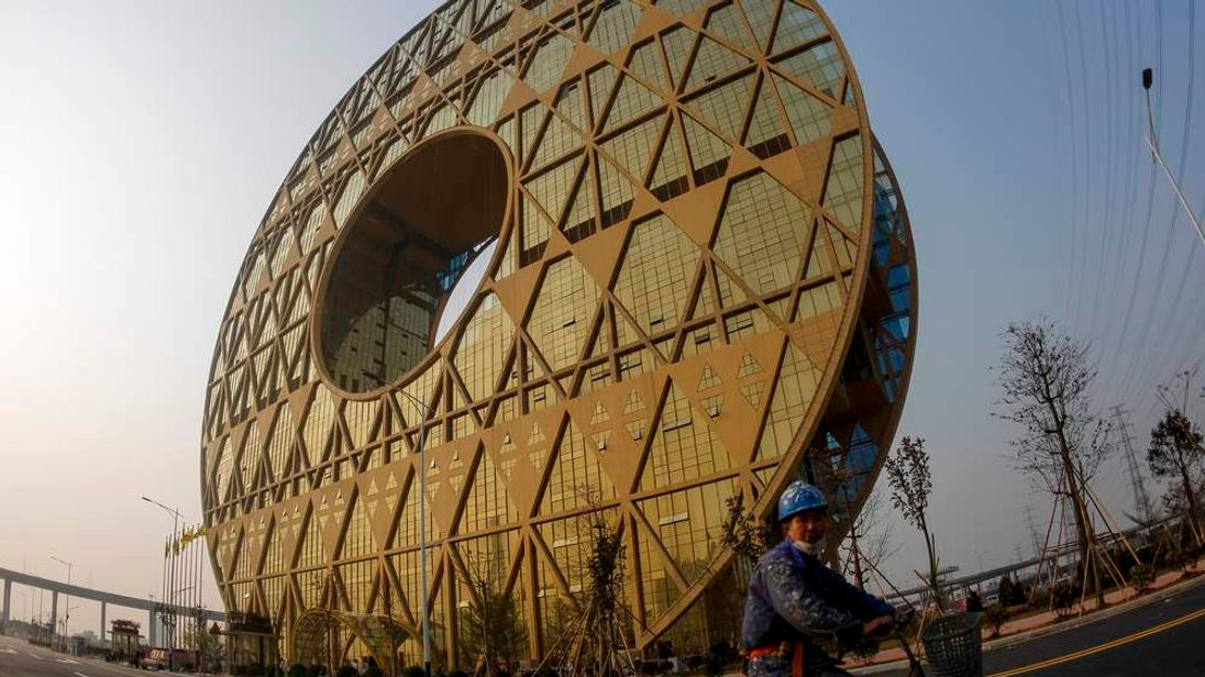 A labourer cycles past the newly built Guangzhou Circle building in Guangzhou