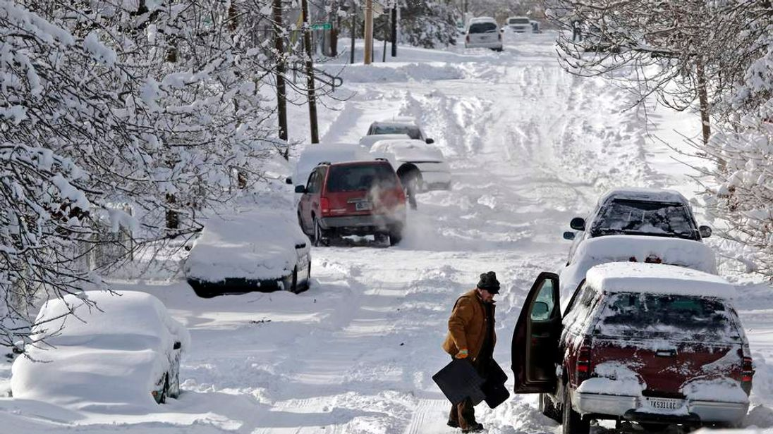 Man clears snow from his car in Indianapolis, Indiana
