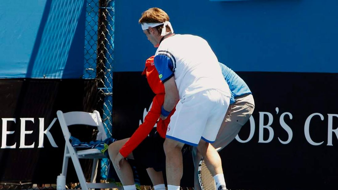 Gimeno-Traver of Spain assists an official in helping a ball boy who collapsed during his men's singles match against Raonic of Canada at the Australian Open 2014 tennis tournament in Melbourne