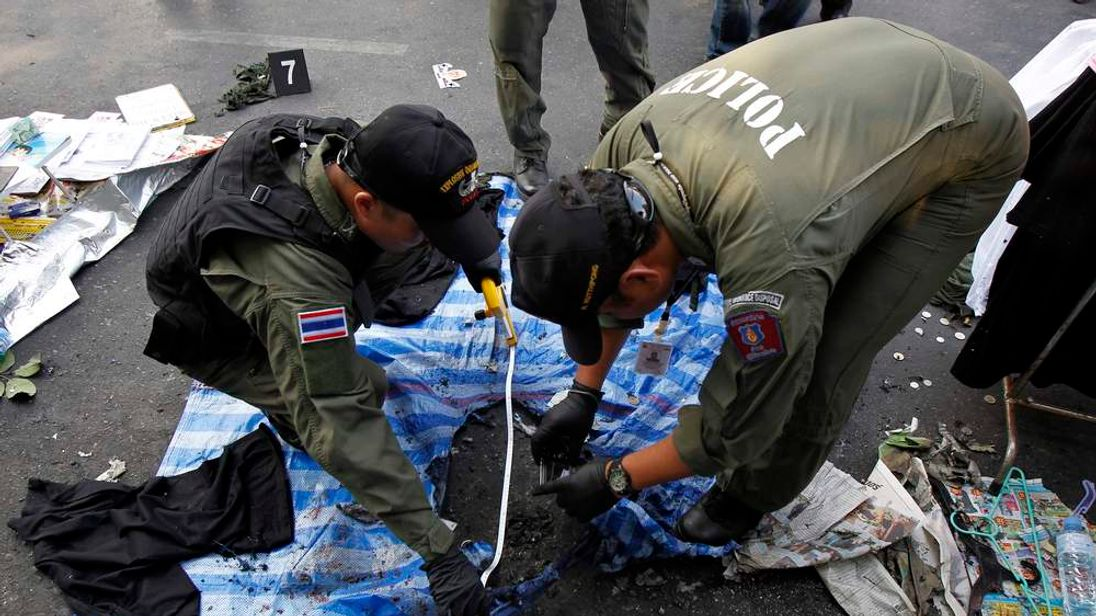 Thai policemen check the scene following an explosion near a camp of anti-government protesters at the Victory monument in central Bangkok