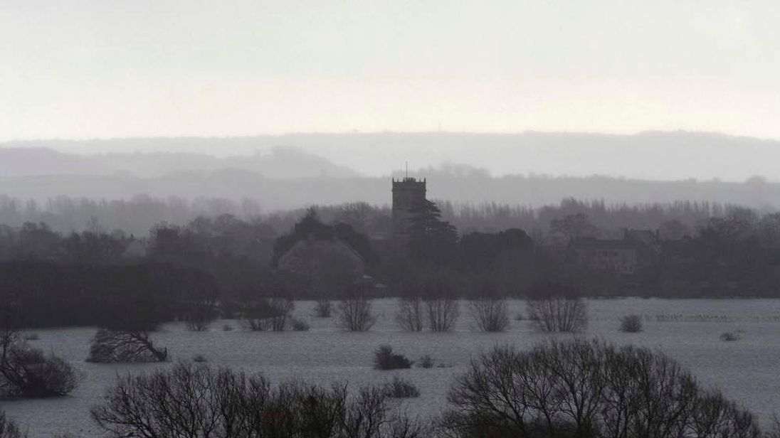 Rain falls as the village of Muchelney is seen on the flooded Somerset Levels, near Langport in south west England