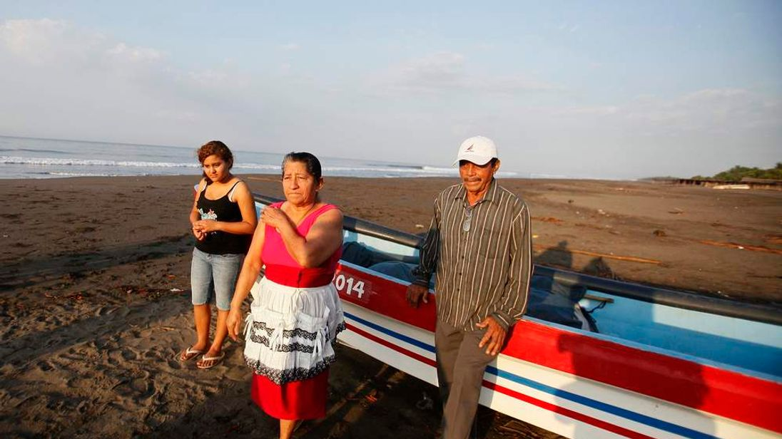 The family of castaway fisherman Jose Salvador Alvarenga stand near a boat in the fishing town of Ahuchapan
