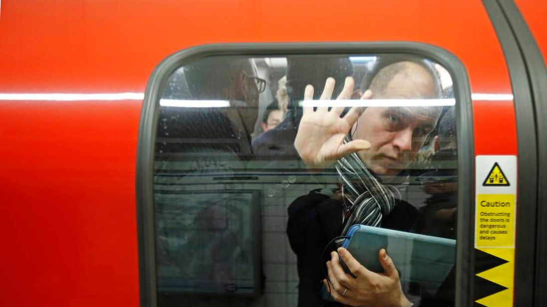 A passenger is squeezed up against a door in one of the few tube trains which became overcrowded during rush hour at Oxford Circus underground station in London