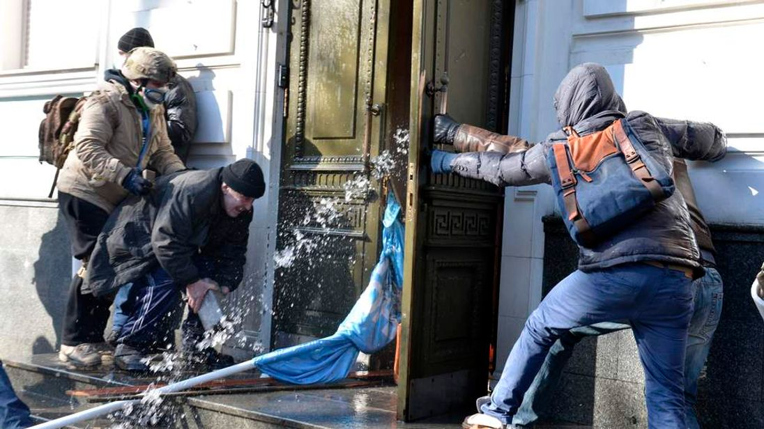 Anti-government protesters throw stones as they attack an office of the pro-presidential Party of the Regions in Kiev