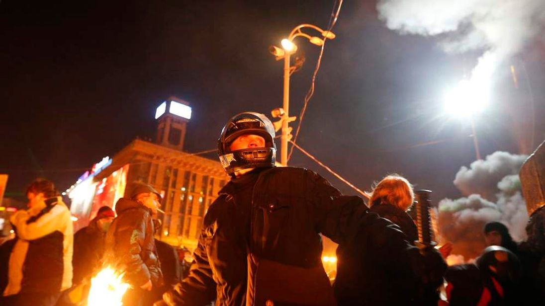 An anti-government protester prepares to throw a petrol bomb during clashes with riot police at Independence Square in Kiev
