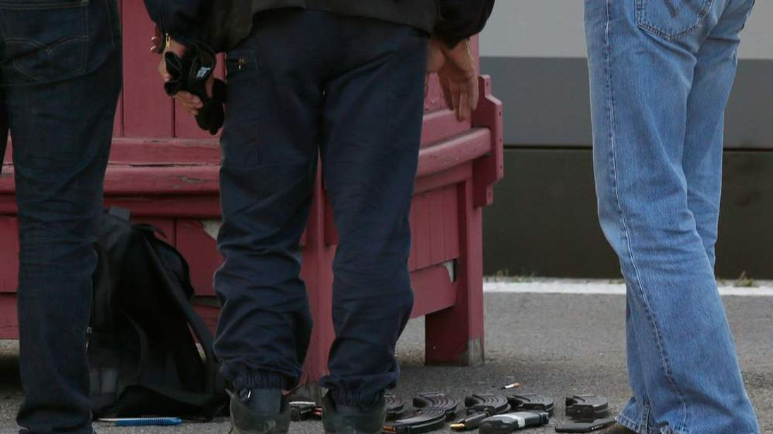 French judicial police stand on the train platform near weapon cartridges and a backpack in Arras after shots were fired on a Thalys high-speed train