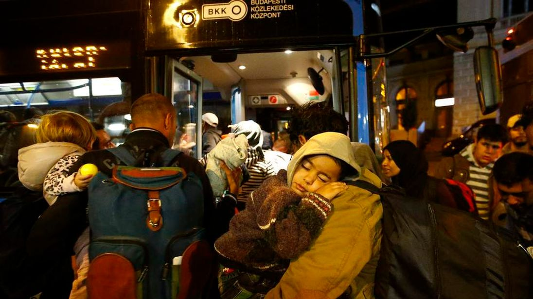 Migrants enter a bus, which is supposed to leave to Austria and Germany, at the Keleti trainstation in Budapest