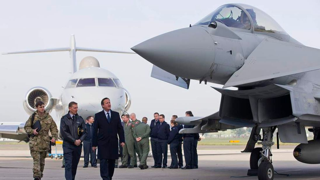 Britain's Prime Minister David Cameron looks at an RAF Eurofighter Typhoon fighter jet during his visit to Royal Air Force station RAF Northolt in London