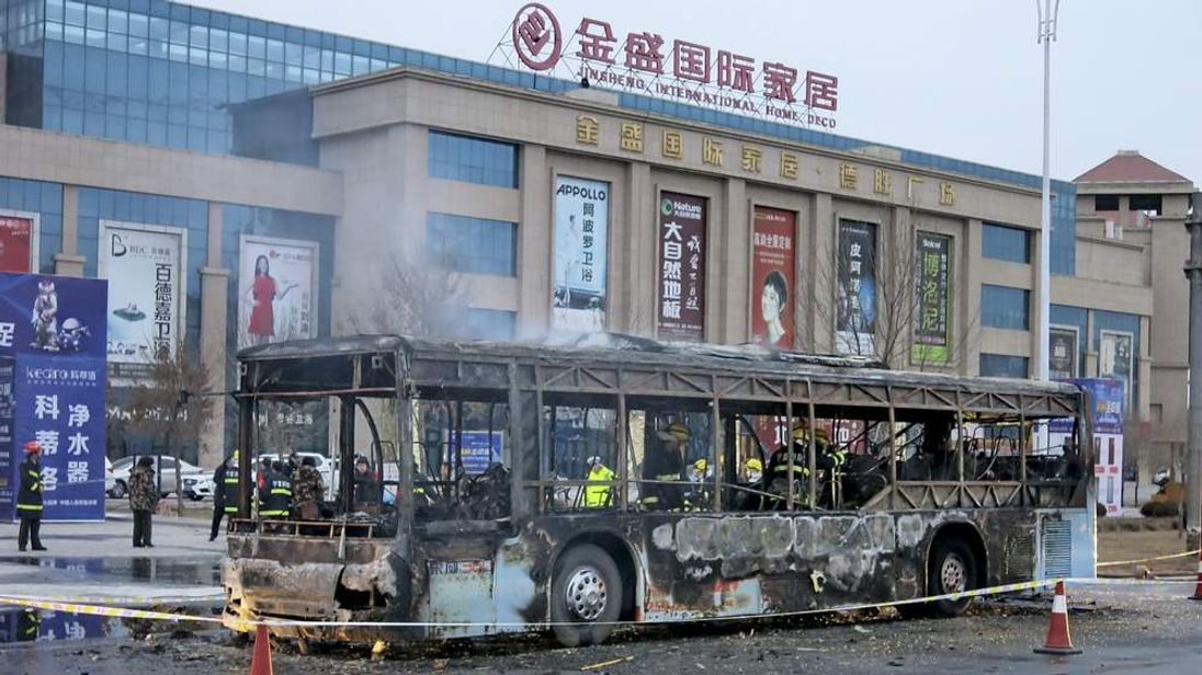 Firefighters are seen working inside a burnt bus after a fire on a street in Yinchuan