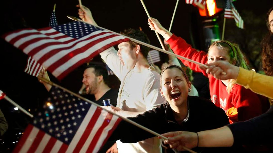 People wave US flags while cheering as police drive down Arlington Street in Watertown