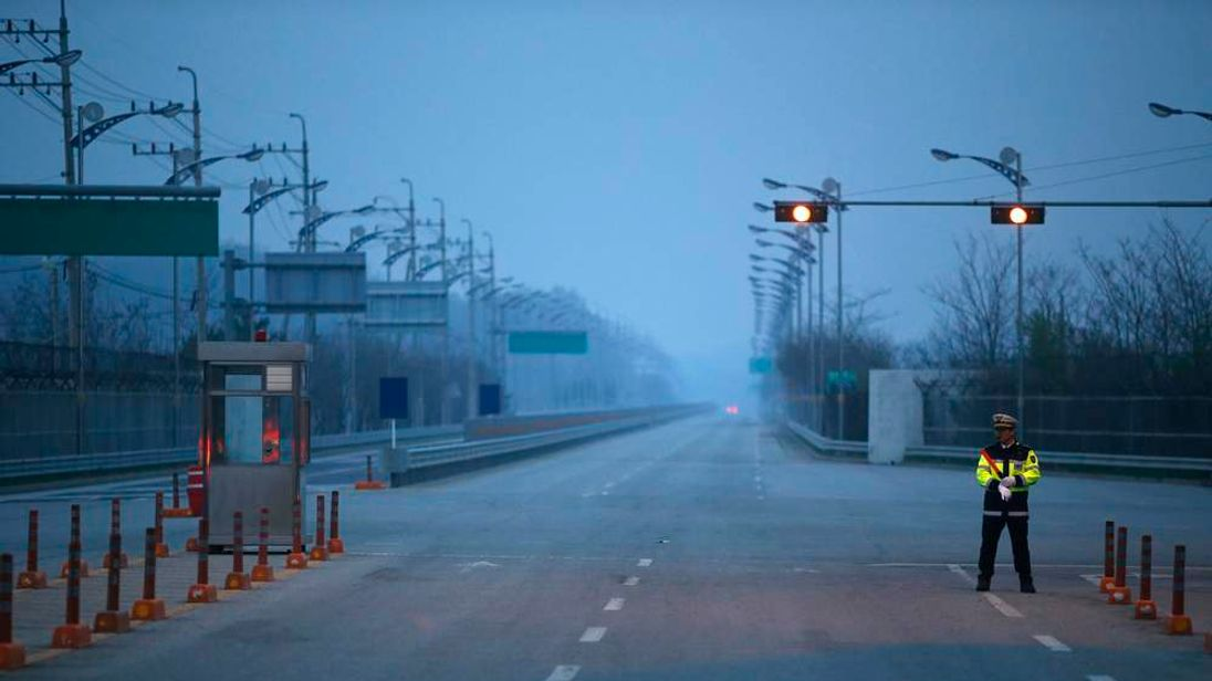 A South Korean police officer stands guard on an empty road connecting the Kaesong Industrial Complex (KIC) inside the North Korean border with the South's CIQ in Paju